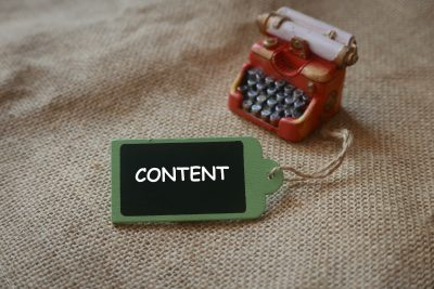 a red miniature of vintage typewriter with wooden tag written with content