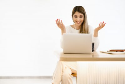 happy sfemale blogger laughing while chatting with friends in social networks on laptop device