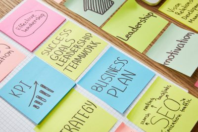 paper stickers with words teamwork, business plan and seo on tabletop