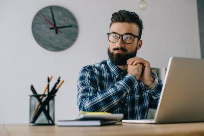 thoughtful young seo looking away while sitting at workplace with laptop