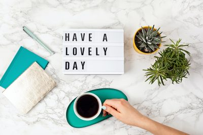 Flat lay with lightbox with text Have a lovely day and coffee cup. Social media, motivation quote