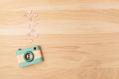 Flat lay with toy wooden camera and hearts. Social media, posts, likes, followers, online