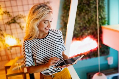 Portrait of cheerful woman using portable pc for blogging in social networks