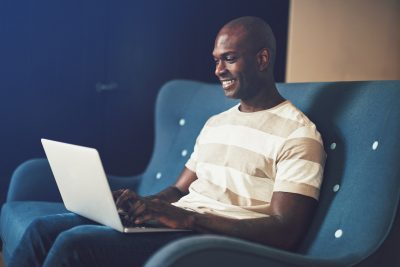 Smiling African entrepreneur working online while sitting on a sofa