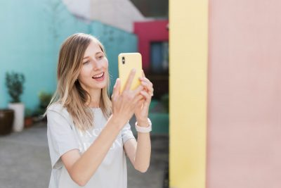 Young woman using social media or video chat via mobile phone near bright and colorful wall outdoor